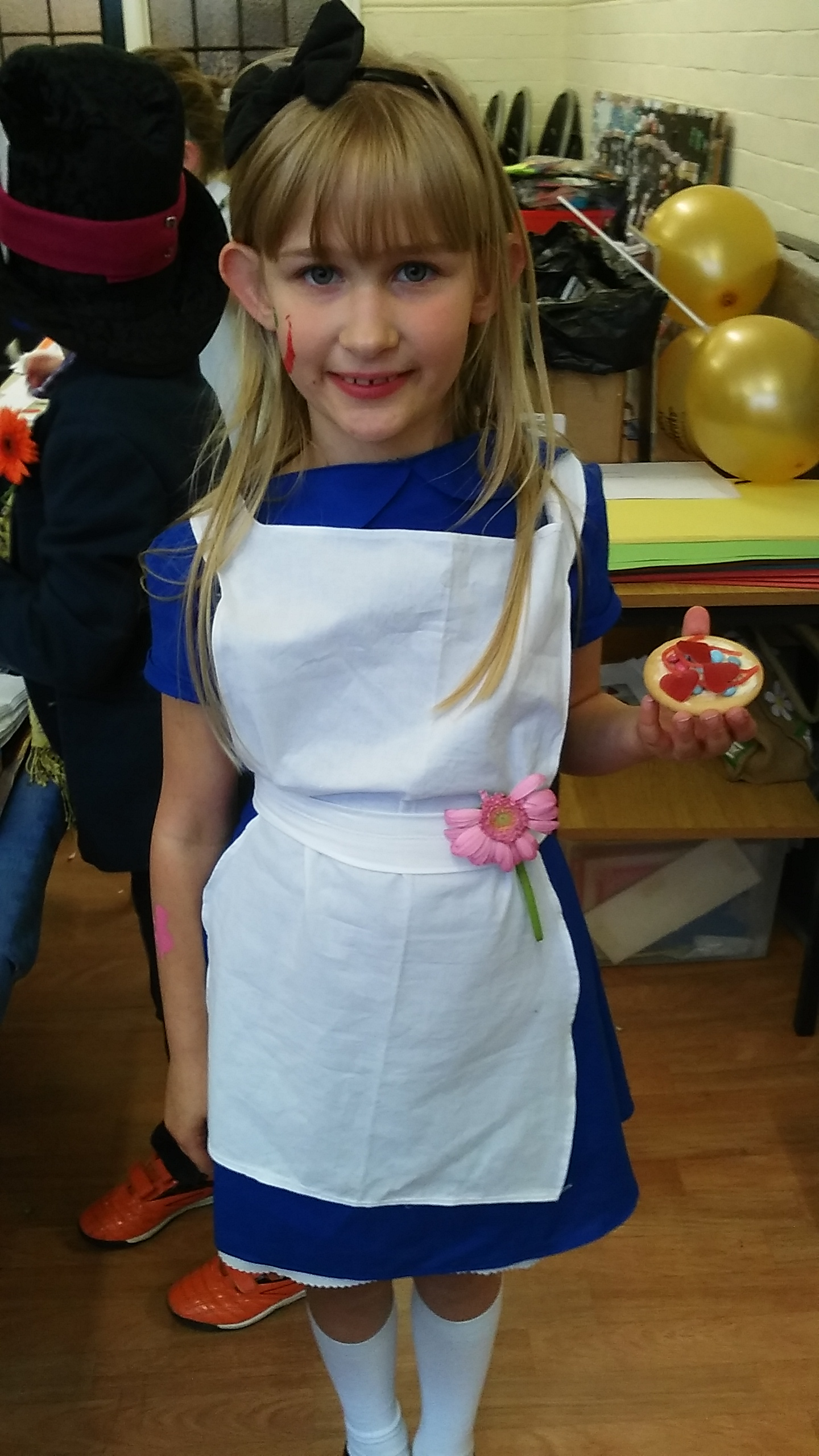 Young girl holding a decorated biscuit whilst dressed as Alice in Wonderland.