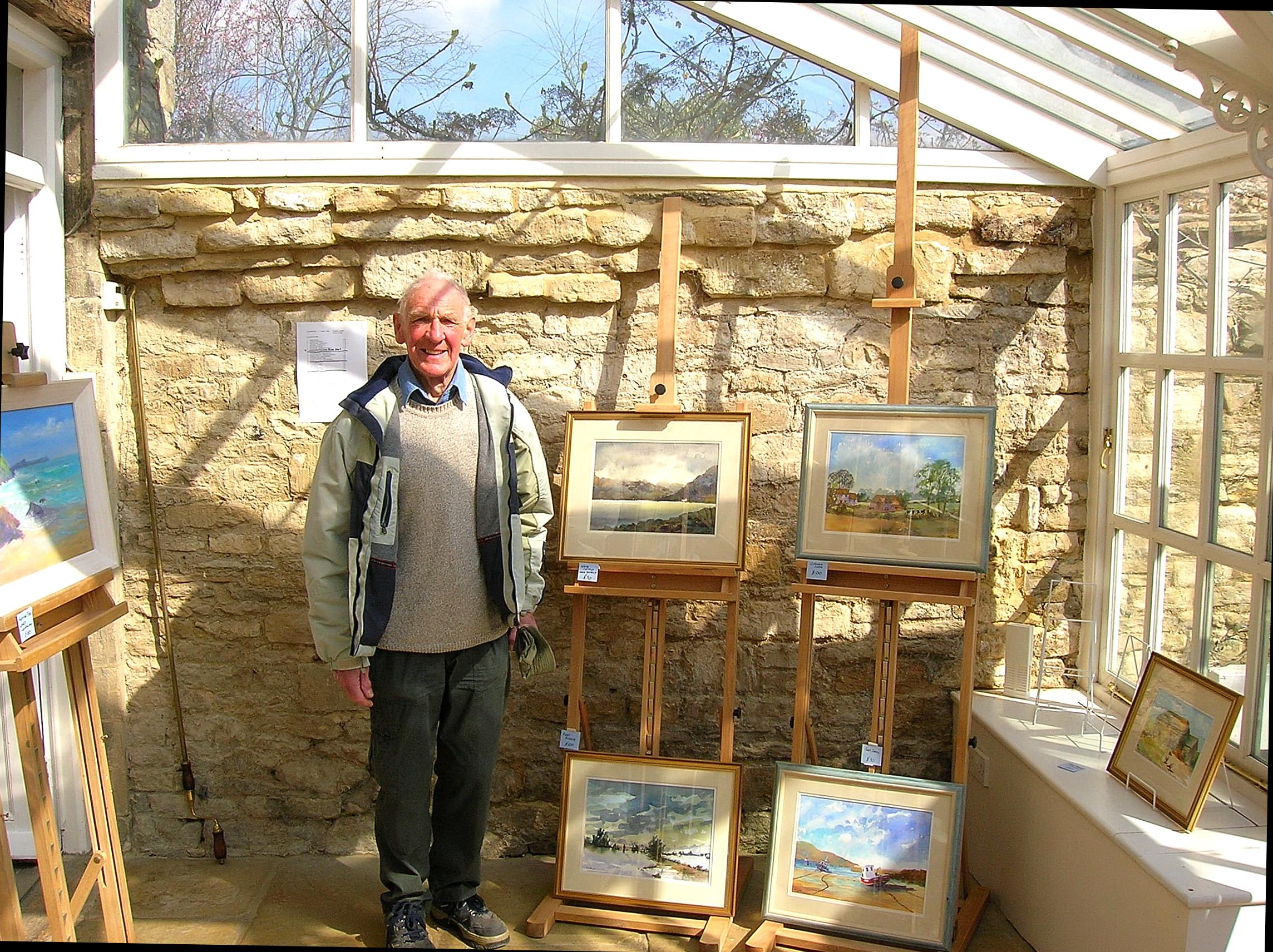 Derek stands inside a conservatory surrounded by easels displaying some of his paintings