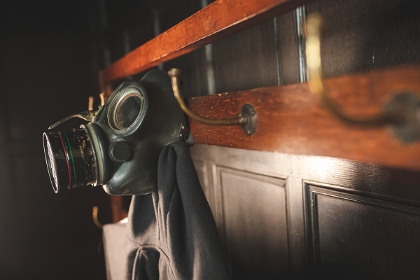 A photograph of a gas mask hanging on a coat rack
