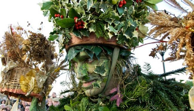 Photo of someone dressed as the 'green man', a man with green skin and covered in leaves.