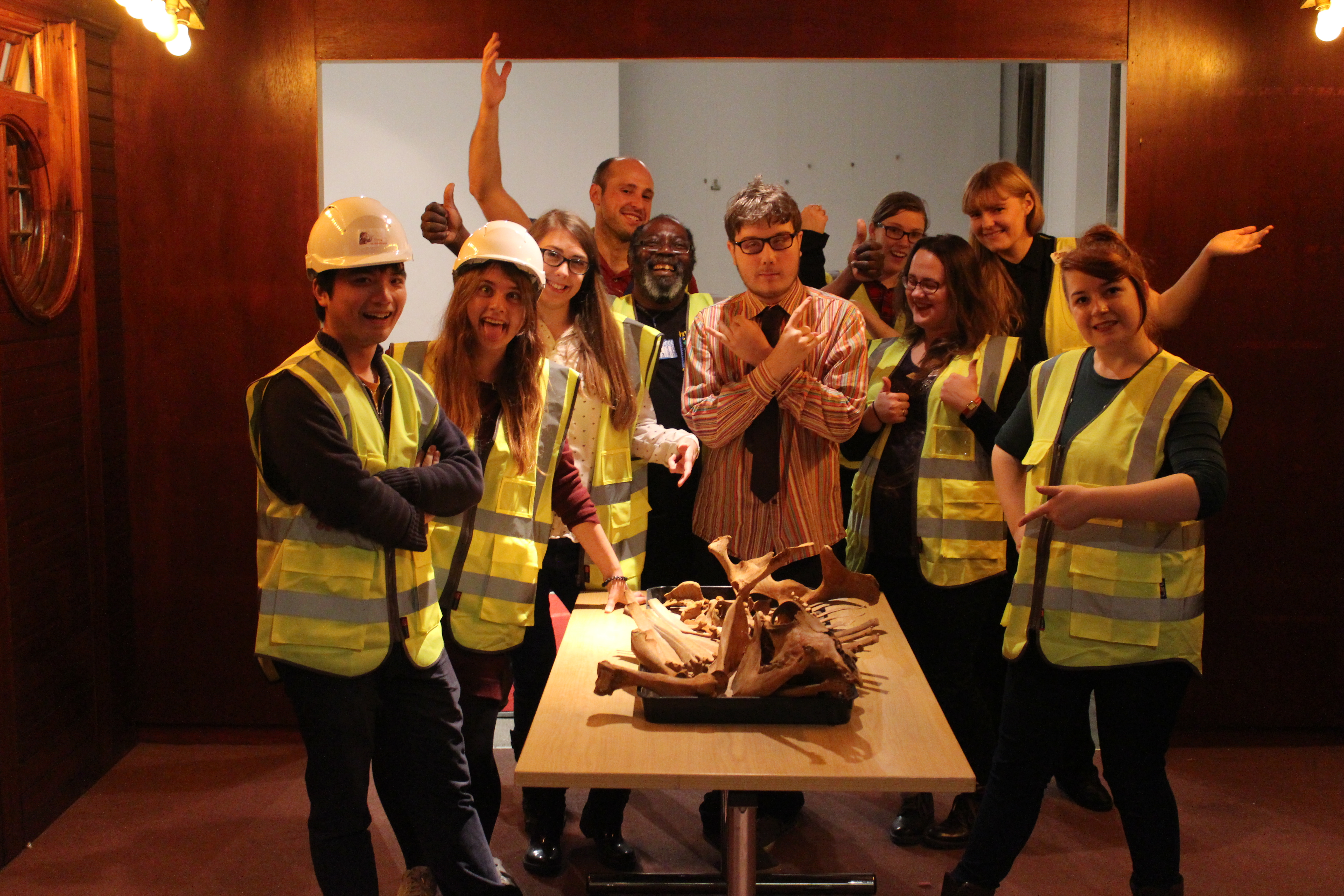 Photo of young volunteers in the Museum with high vis jackets and hard hats on during an event called Oxcavation
