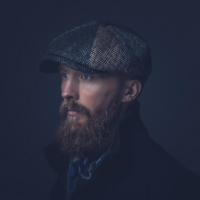 A photographic portrait by Ian Wallman, a young man with a large, light brown beard stands against a dark backdrop wearing a tweed flat cap and navy blue coat