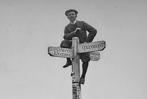 A Victorian photograph of a man sitting on top of a directional sign post