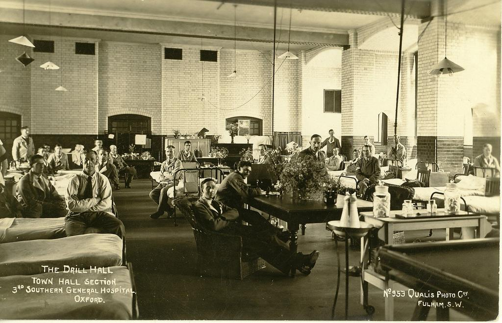 What is now a gallery space in the Town Hall being used as a military hospital during WW1, soldiers are seen sitting at tables and beside their beds