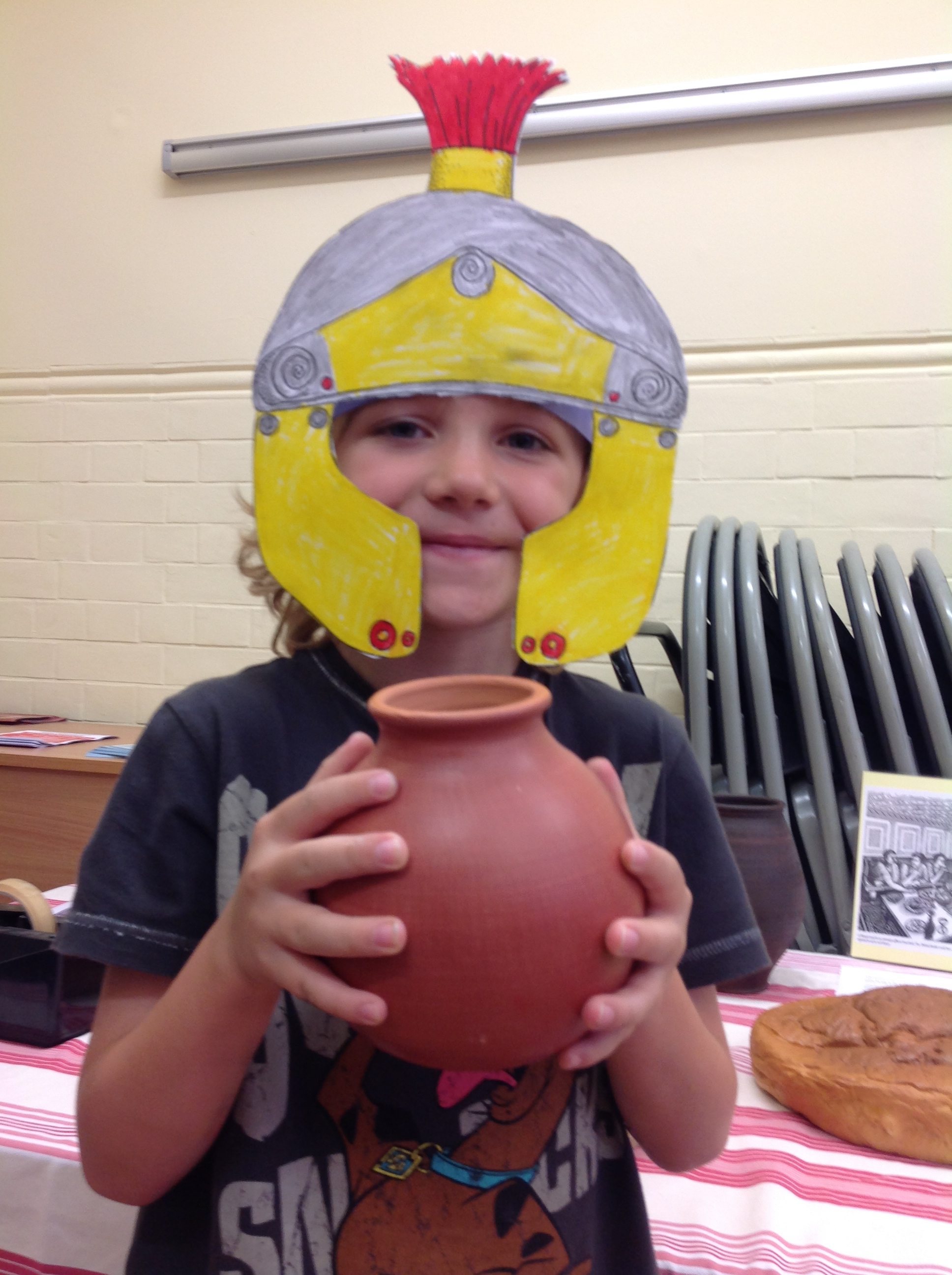 Photograph of a young boy holding a Roman style pot