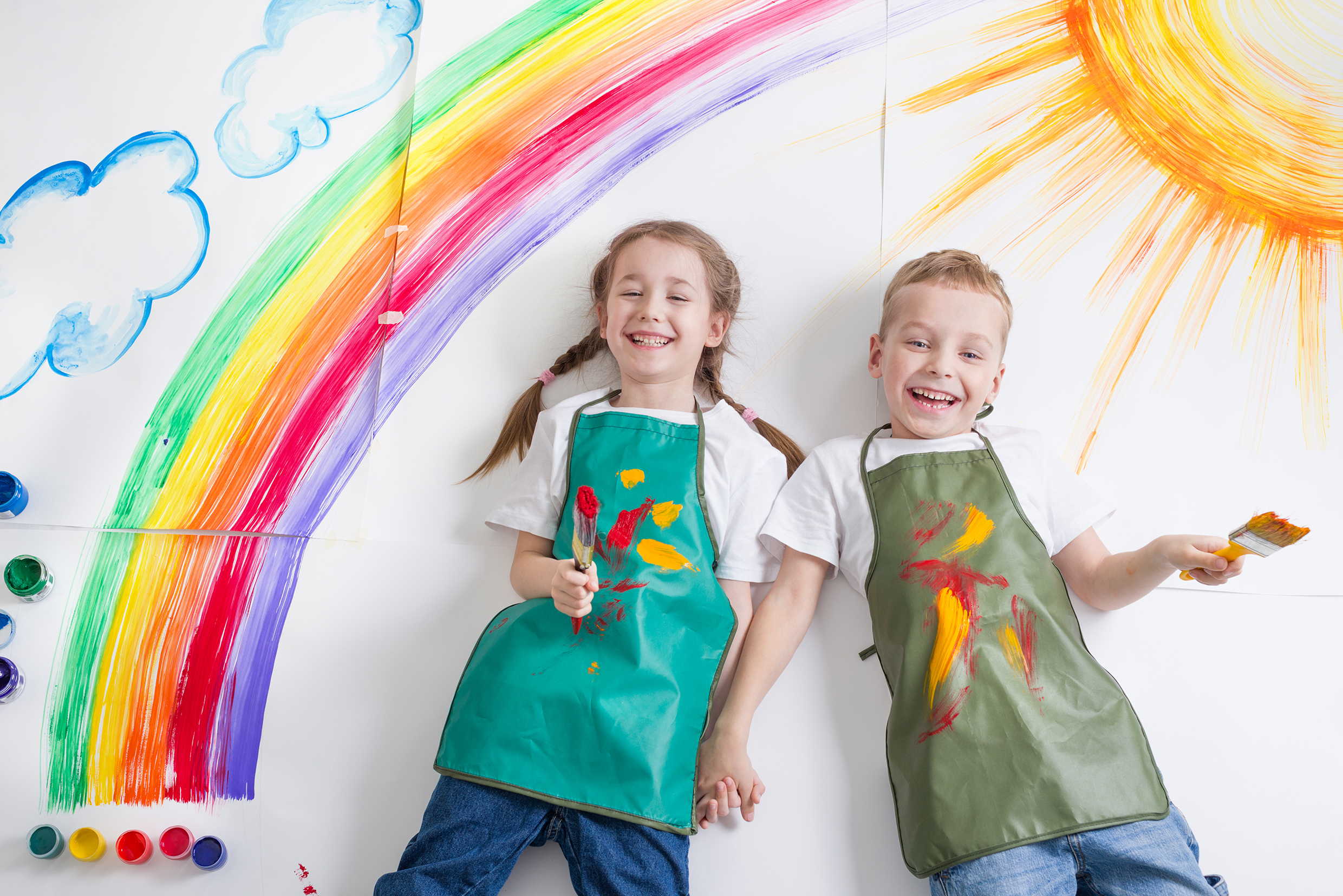 Photograph of two children with aprons on standing under a painted rainbow.