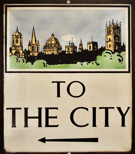 A metal sign that says 'to the city' with an arrow and image of Oxford's skyline.