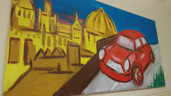 A painted Oxford skyline in vivid colours showing the spires and Radcliffe camera in the background. A red mini is painted in the foreground.