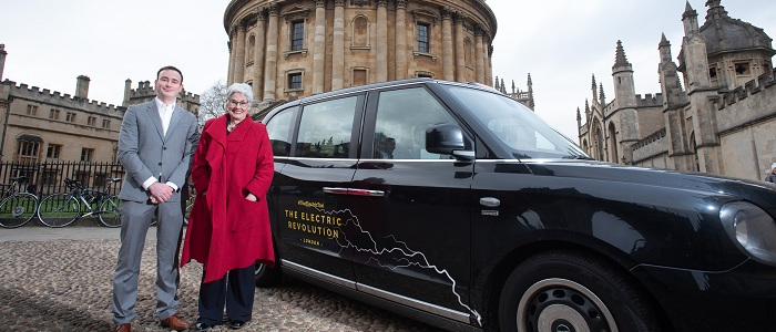 Picture of Councillors Tom Hayes and Yvonne Constance, from Oxford City Council and Oxfordshire County Council respectively, with an electric Hackney taxi in front of the Radcliffe Camera in Oxford.