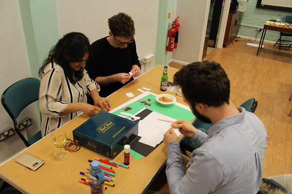 Three people at a table creating a board game