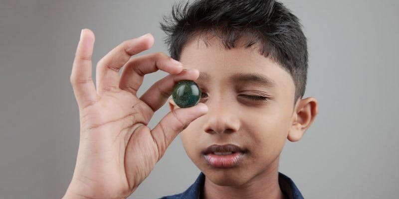 A boy looking at a marble.