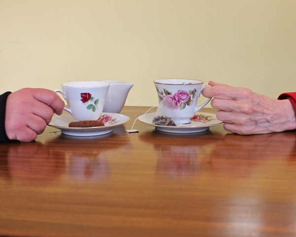 A photograph of two people holding cups of tea